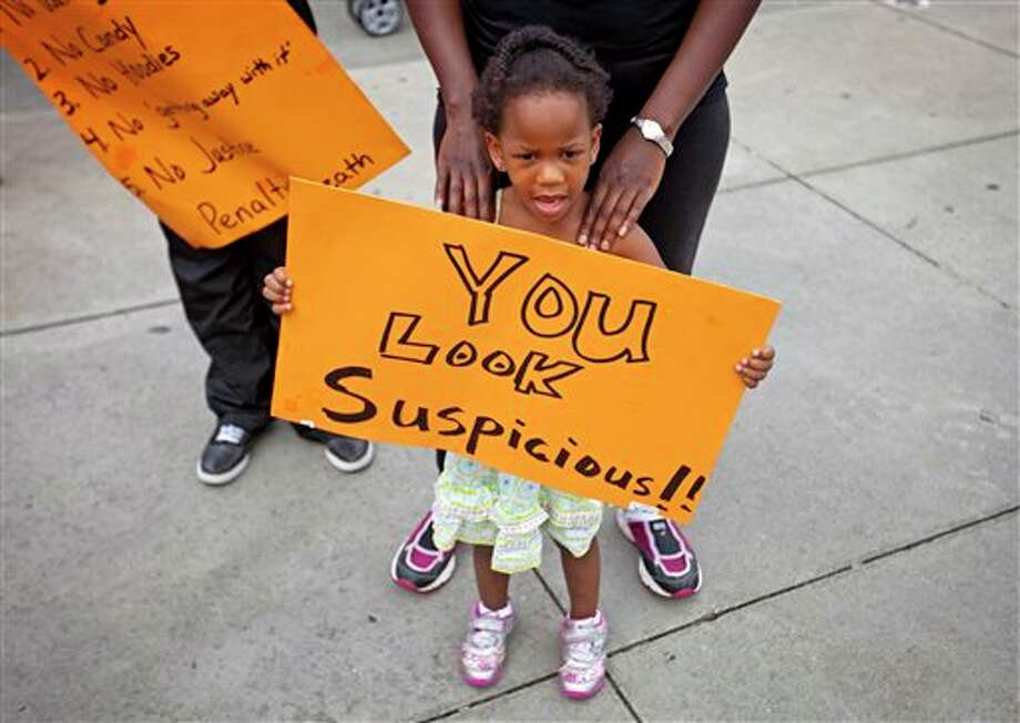 Jebiah Jones, 3, holds a sign as her mother Keiota Jones, stands behind her during a protest the day after George Zimmerman was found not guilty in the 2012 shooting death of teenager Trayvon Martin, Sunday, July 14, 2013, in Atlanta. (AP Photo/David Goldman) Photo: David Goldman / AP