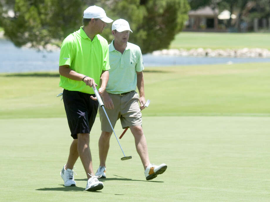 Brady Shivers (left) and Terence Begnel (right) walk off the green after putting during day 2 of the Green Tree Jamboree Saturday at Green Tree Country Club. James Durbin/Reporter-Telegram Photo: JAMES DURBIN
