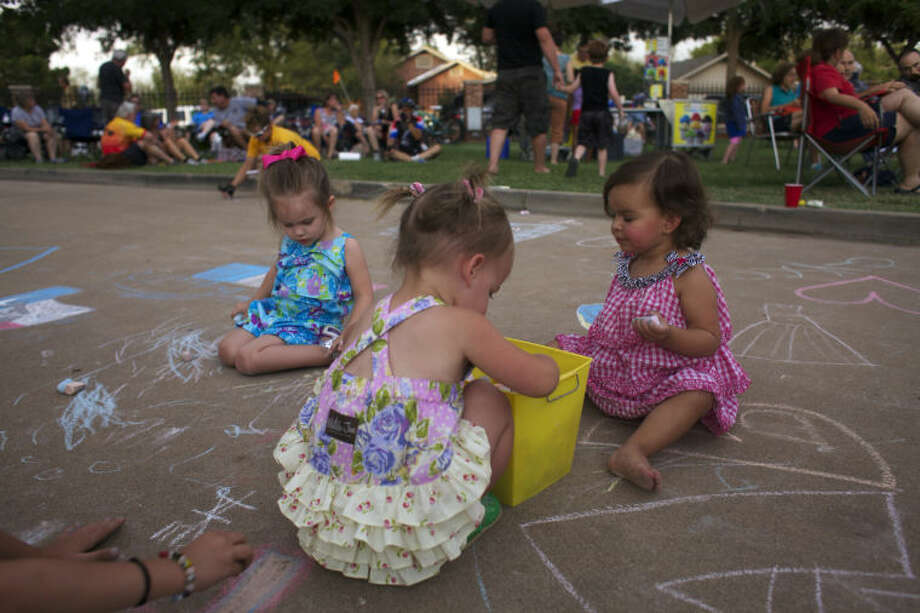 June Hurst, Brielle Barcum, and Mica Welch (L-R) draw with sidewalk chalk during the Museum of the Southwest's Summer Sunday Lawn concert. Photo: MARY POWERS