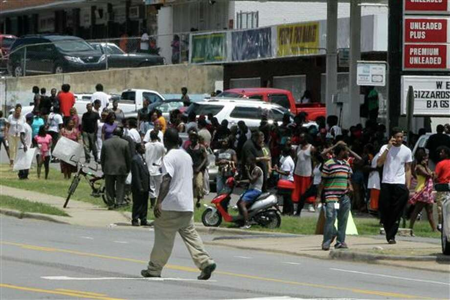 A man walks past a crowd gathered near the site of a fatal shooting in Little Rock, Ark., Monday, July 15, 2013. A man was shot by Little Rock police after he ran following a traffic stop that officers made because the man was driving an allegedly stolen SUV. (AP Photo/Danny Johnston) Photo: Danny Johnston / AP
