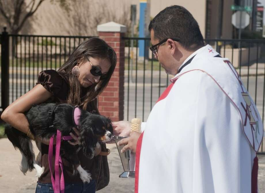 The Rev. Rick Lopez blesses Charlei as Cathy Guebara holds her during the annual Pet Blessing ceremony on Oct. 4 at St. Ann's School. Tim Fischer\Reporter-Telegram Photo: Tim Fischer