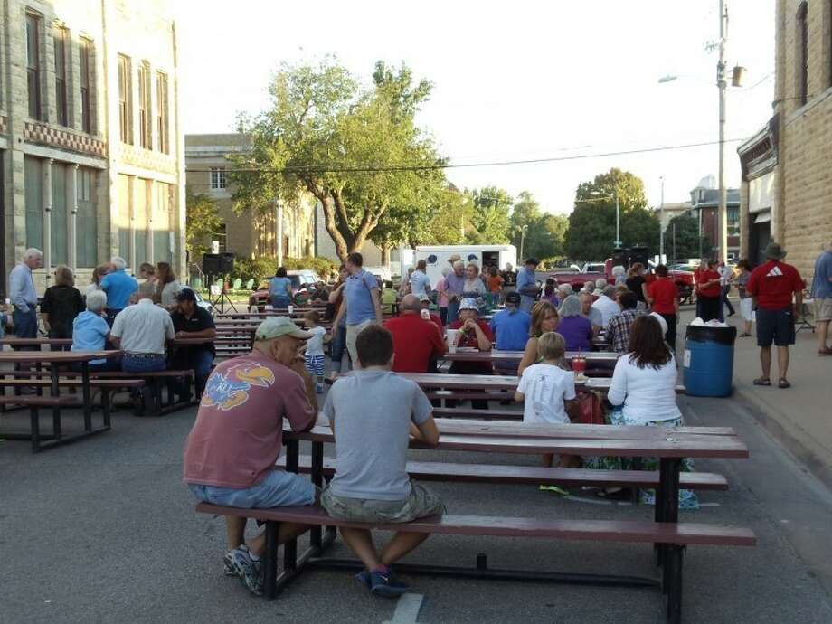 People gather to eat at picnic tables in Winfield, Kan., during the annual Walnut Valley Festival. Photo: Joan Huff