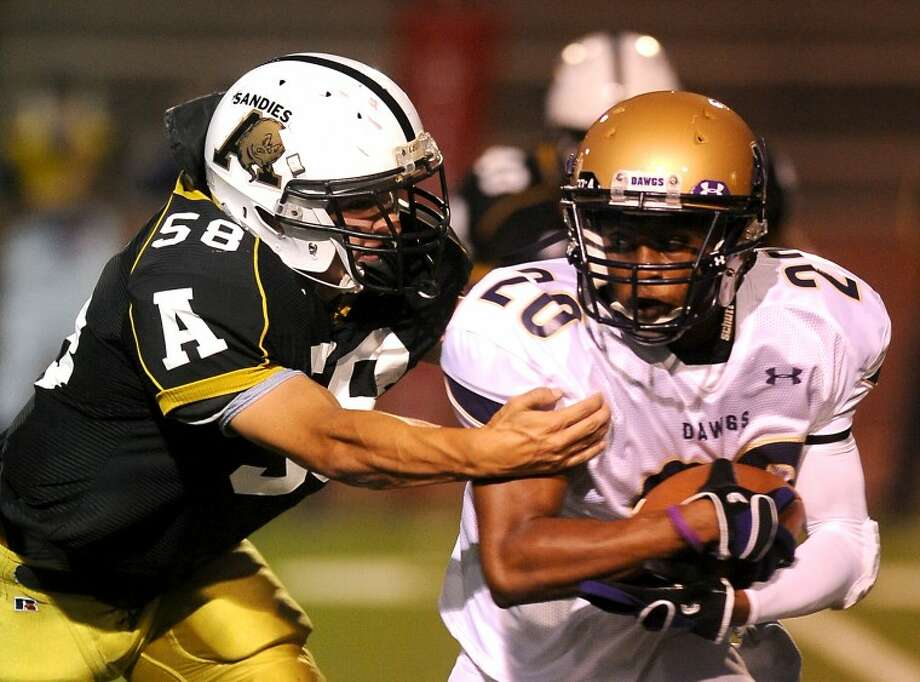 Michael Norris / Amarillo Globe-News Jacoby Webster (20), Midland, gets chased down in the backfield by Robert York (58), Amarillo, for a loss of yards during the Midland High Bulldogs and Amarillo High Sandies game Friday, August 26, 2011 at Dick Bivins Stadium. Photo: Michael Norris / Amarillo Globe-