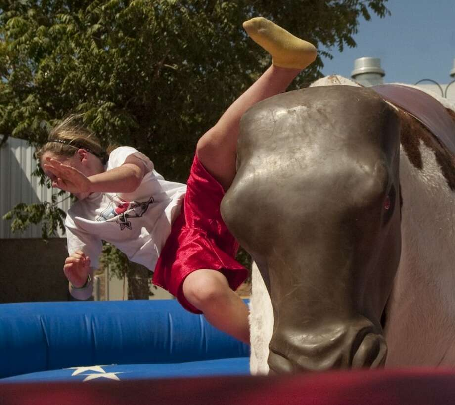 Abby Jordan, 10, takes a fall off the mechanical bull Saturday at the Midland County Fair. Photo by Tim Fischer/Midland Reporter-Telegram Photo: Tim Fischer