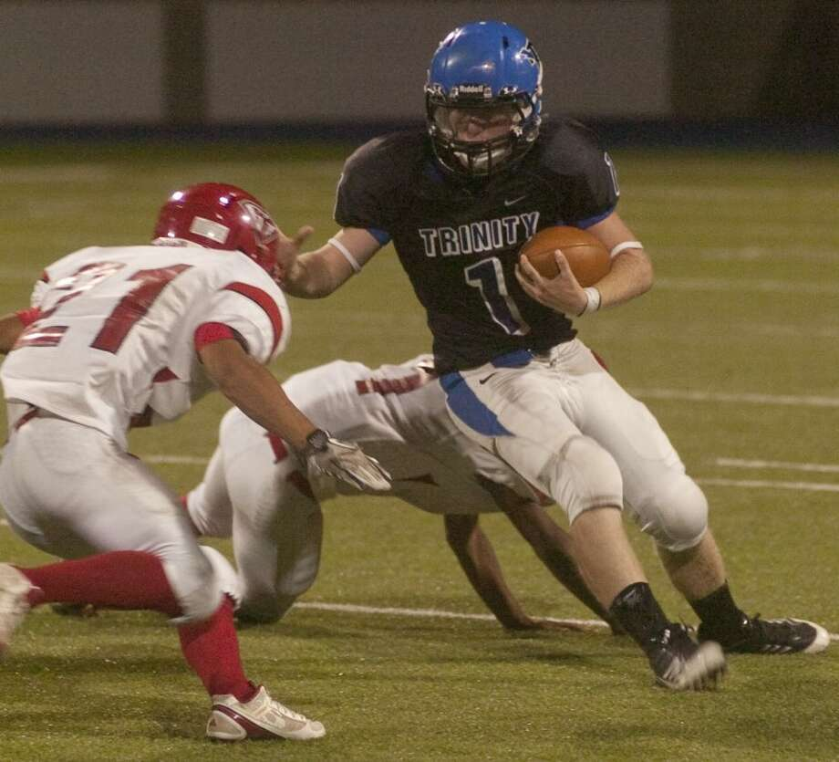 Trinity's Aaron Watson gets past Grandfalls Royalty's Gilbert Nunez and tries to get past Junior Marquez Saturday night at Grande Communications Stadium during the 2011 ASCO Midland Football Madness. Photo by Tim Fischer/Midland Reporter-Telegram Photo: Tim Fischer