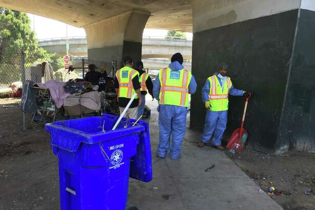 City cleanup crews, counselors and police clear out a large camp of homeless people on Cesar Chavez Street around Highway 101.