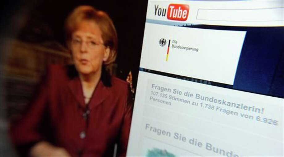 FILE- This Dec.31, 2008 file photo taken through a magnifying glass shows a video of German Chancellor Angela Merkel delivering her New Year's speech beside the Youtube channel of the German government. YouTube announced Monday, Oct. 8, 2012, that it is extending its original programming initiative into Europe, with at least 60 new video channels from media companies including Britain's BBC, London-based FreemantleMedia and the Netherlands' Endemol. The Google Inc.-owned video site said Monday it is launching more than 60 new video channels with content from Britain, Germany, France, and the United States. (AP Photo/dapd, David Hecker, File) Photo: David Hecker / DAPD