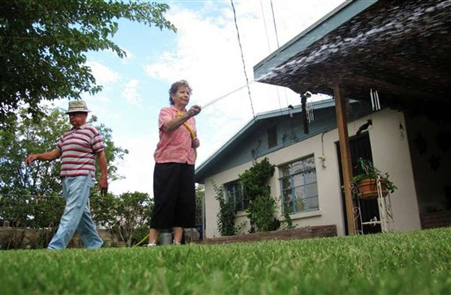 In this Aug. 13, 2011 photo, Soledad Fierro waters the grass while her husband Fred walks in their backyard in El Paso, Texas . A two-decades-old water ordinance that led many El Paso residents to replace their lawns with desert landscaping and comply with measures to conserve water is paying off during one of Texas' worst droughts. Today, El Paso is among the few cities in the drought-stricken state not worrying about water. (AP Photo/Juan Carlos Llorca) Photo: Juan Carlos Llorca / AP