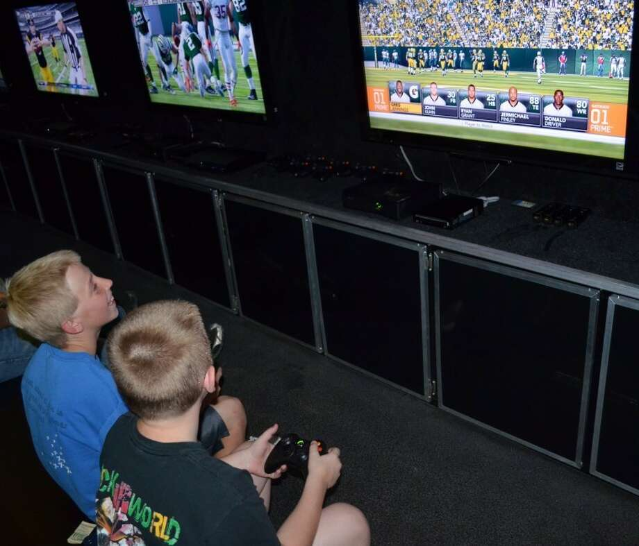 Dylan Dimmig, 10, and Cole Hayes, 11, compete in the second round of fixtures in Midland's first Madden NFL 12tournamentSaturday night at the Hollywood Theater.