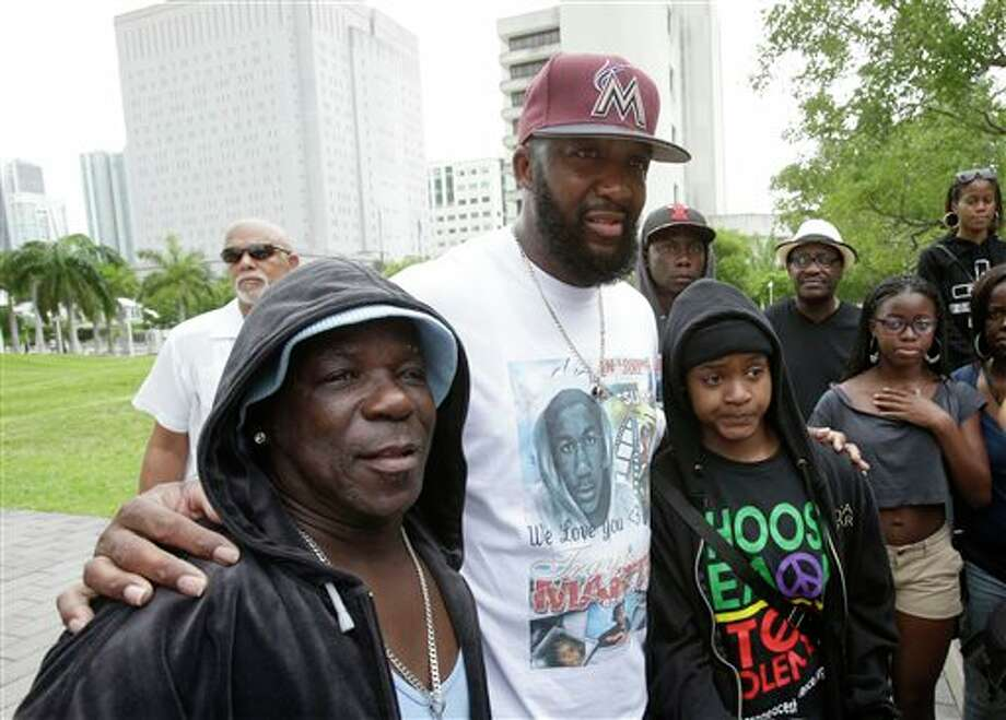 "Tracy Martin, center, father of Trayvon Martin, poses for photos with supporters wearing hoodies, at a ""Justice for Trayvon"" rally, Saturday, July 20, 2013 in Miami, one week after George Zimmerman was found not guilty in the shooting death of unarmed teenager Trayvon Martin. (AP Photo/Wilfredo Lee) Photo: Wilfredo Lee / AP"