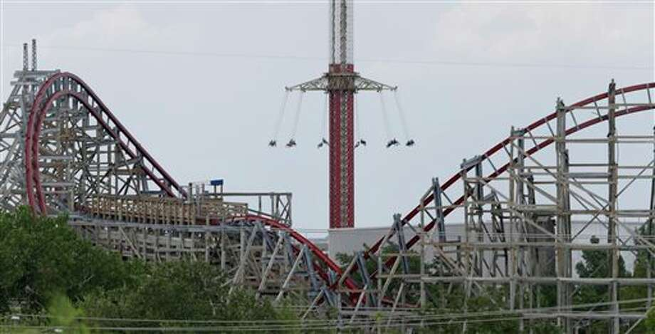 The Texas Giant roller coaster ride sits idle in the foreground as people take in another ride a the Six Flags Over Texas park Saturday, July 20, 2013, in Arlington, Texas. Investigators will try to determine if a woman who died while riding the roller coaster at the amusement park Friday night fell from the ride after some witnesses said she wasn't properly secured.(AP Photo/LM Otero ) Photo: LM Otero / AP