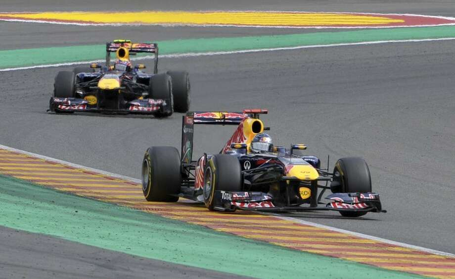 Red Bull driver Mark Webber of Australia, background, chases Red Bull driver Sebastian Vettel of Germany during the Belgian Formula One Grand Prix in Spa-Francorchamps, Sunday, Aug. 28, 2011. Red Bull driver Sebastian Vettel of Germany won the race, Red Bull driver Mark Webber of Australia placed second, and McLaren Mercedes driver Jenson Button of Britain placed third. (AP Photo/Geert Vanden Wijngaert) Photo: Geert Vanden Wijngaert