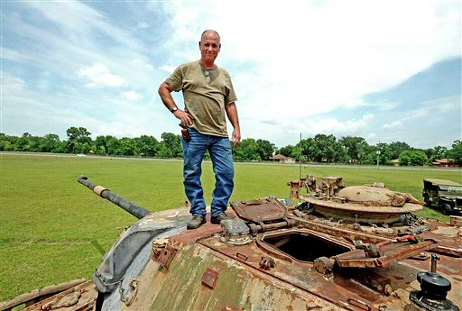 In this July 11, 2013 photo, Gary Giarraputo stands with his 1963 British Chieftain Mk 10 tank that is being restored in Beaumont, Texas. More than 25 machines and pieces of gear make up the beginnings of his vision for a Southeast Texas military ?museum. (AP Photo/Beaumont Enterprise, Randy Edwards) Photo: Randy Edwards / Beaumont Enterprise