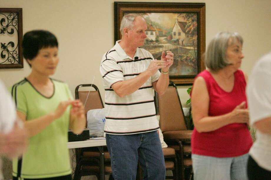 "Curtis Gifford watches as Pok-Duk Kim, left, and Criss Kohl ""Cut-a-Rug"" line dance Thursday during dance class at the Midland Senior Center. Cindeka Nealy/Reporter-Telegram Photo: Cindeka Nealy"