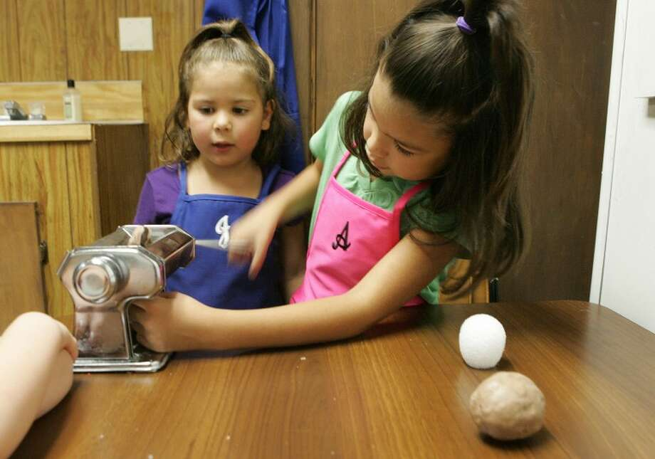 Jaslyn Velez, 5, left, watches as her sister, Ashtyn, 7, flattens fondant that will be used to make rocks for her mermaid cake Tuesday at Tall City Sweets. Cindeka Nealy/Reporter-Telegram Photo: Cindeka Nealy