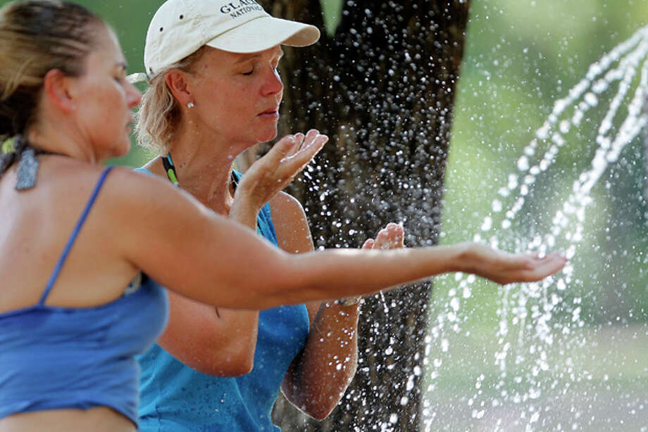 Jodi Tollleson (left) and Patti Newsome of Mineral Wells, Texas cool down at Burger's Lake, Tuesday August 2, 2011 in Fort WWorth, Texas. A health official says 12 people in Dallas have died from the heat this summer, already three more than last year's total with the hottest month still ahead. (AP Photo/The Fort Worth Star-Telegram, Ron Jenkins) Photo: Ron Jenkins / Fort Worth Star-Telegram Ron Jenkins