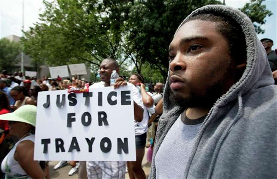"""Ibn Akbar from Boston, Mass., right, joins a """"Justice for Trayvon -100 City Vigil"""" Saturday, July 20, 2013, as they demonstrate in front of the federal court in Washington. Friday, just before the scheduled """"Justice for Trayvon"""" vigils and rallies in 100 U.S. cities, President Barack Obama talked to a nation rubbed emotionally raw in the week since the man who shot and killed 17-year-old Trayvon Martin was acquitted in a Florida courtroom. Civil rights activist Al Sharpton, organizer of the demonstrations, said the fact that Obama weighed in about stand-your-ground laws, the focus of those demonstrations, will help """"set a tone for both direct action, and needed dialogue."""" (AP Photo/Manuel Balce Ceneta) Photo: Manuel Balce Ceneta / AP2013"""