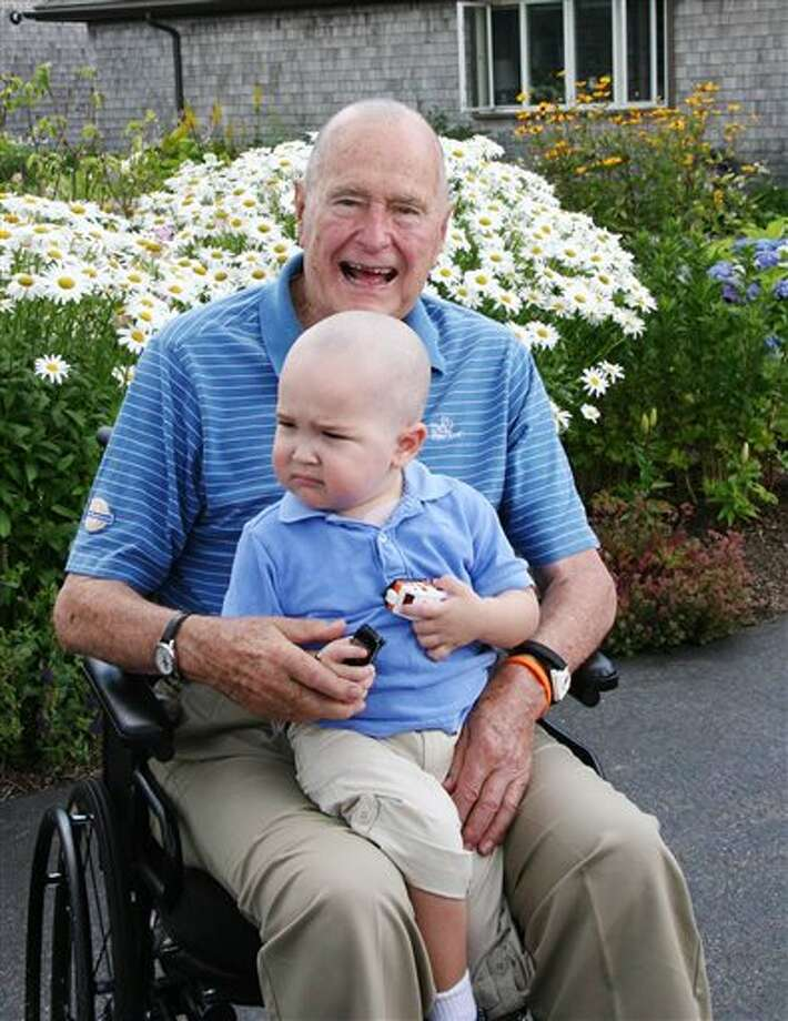 This Wednesday July 24, 2013 photo provided by the Office of George Bush shows President George H. W. Bush with Patrick (last name withheld at family's request), 2, in Kennebunkport, Maine. Bush this week joined members of his Secret Service detail in shaving his head to show solidarity for Patrick, who is the son of one of the agents. The child is undergoing treatment for leukemia and is losing his hair as a result. (AP Photo/Office of George Bush) Photo: HONS / Office of George Bush