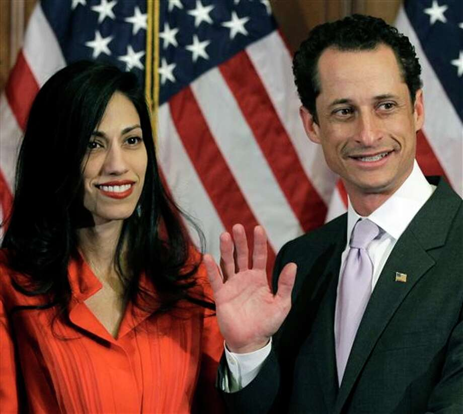 FILE - In this Jan. 5, 2011, file photo, Anthony Weiner and his wife Huma Abedin pose for photographs after the ceremonial swearing in of the 112th Congress on Capitol Hill in Washington. Abedin, who was notably absent five months later when Weiner resigned his congressional seat and admitted sending lewd Twitter photos to women, has been a key player in his surging mayoral run. She's appeared in his campaign launch video, raised tens of thousands of dollars and joined him on the campaign trail. (AP Photo/Charles Dharapak, File) Photo: Charles Dharapak / AP