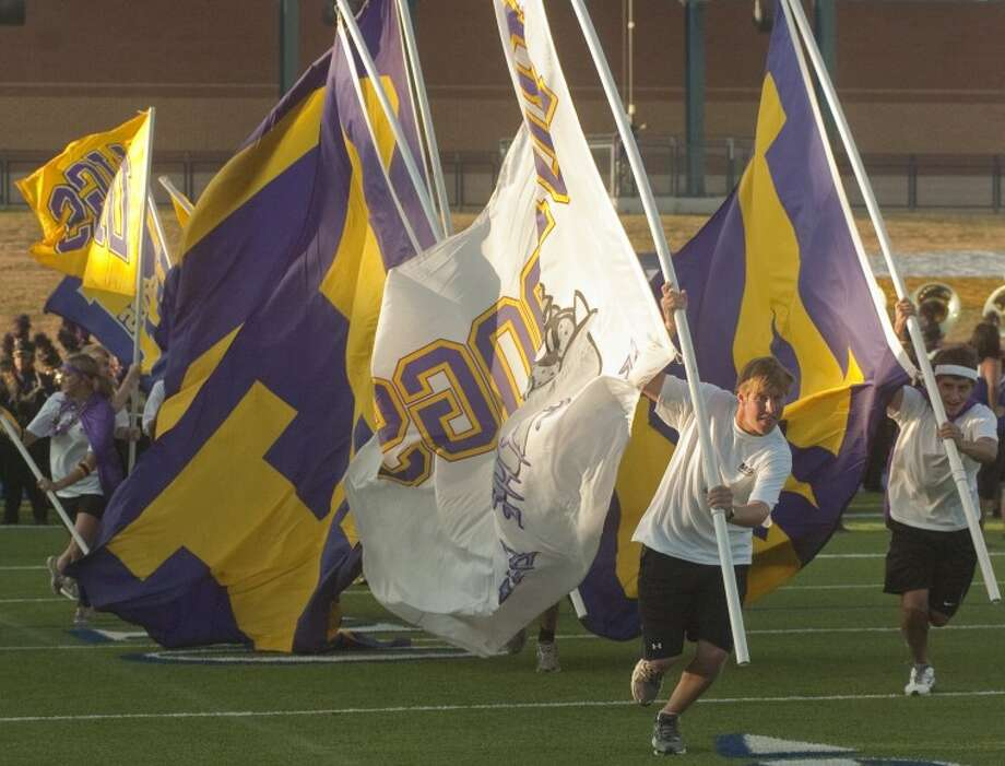 Midland High chear leaders run onto the field Friday night carrying MHS flags to help start the game against El Paso Del Valle. Photo by Tim Fischer/Midland Reporter-Telegram Photo: Tim Fischer
