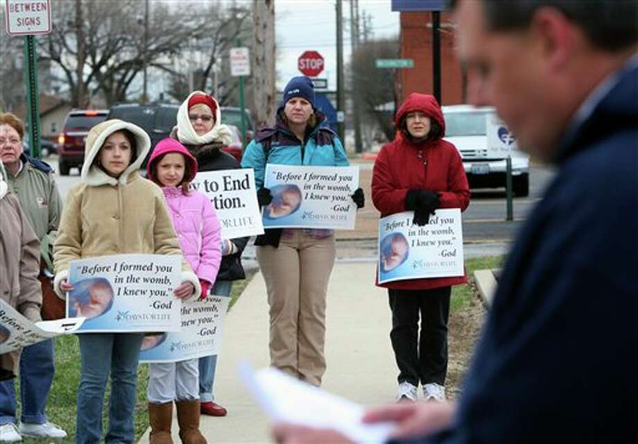 In this March 8, 2011 photo, anti-abortion protesters gather outside the Hope Clinic for Women in Granite City, Ill., as Rev. Chris Comerford, right, from St. Elizabeth's Catholic Church in Granite City speaks out against the abortion clinic. It's legal to get an abortion in America, but in many places it is hard and getting harder. Just this year, 17 states set new limits on abortion; 24 did last year, according to the Guttmacher Institute. Most states now require pre-abortion counseling, and over two dozen require waiting periods. In several of these states, the number of abortions has fallen, pleasing abortion opponents who say the laws are working. (AP Photo/The Telegraph, John Badman) Photo: John Badman / The Telegraph