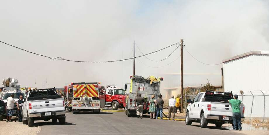 Smoke fills the air as the Midland Fire Department, Odessa Fire Department and Northeast Volunteer Fire Department personnel work at extinguishing a fire Tuesday afternoon at Esquaredi Inc., formerly Engineered Equipment. The fire that destroyed the building was caused by a power line that snagged by a passing semi flatbed truck causing a short. Cindeka Nealy/Reporter-Telegram Photo: Cindeka Nealy