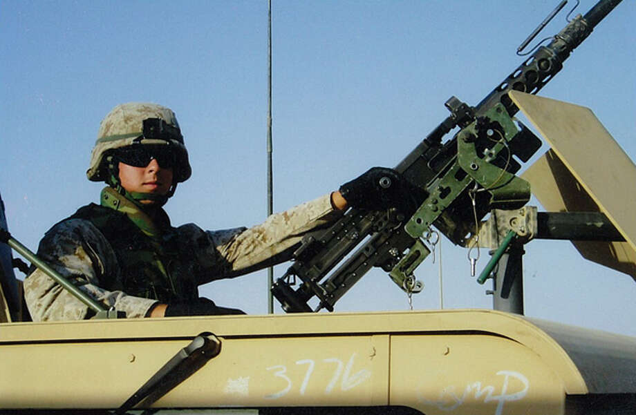 Sgt. Ben Ryburn, who returned to Midland to become a landman, poses next to a .50-caliber gun. Photo: Courtesy Ben Ryburn
