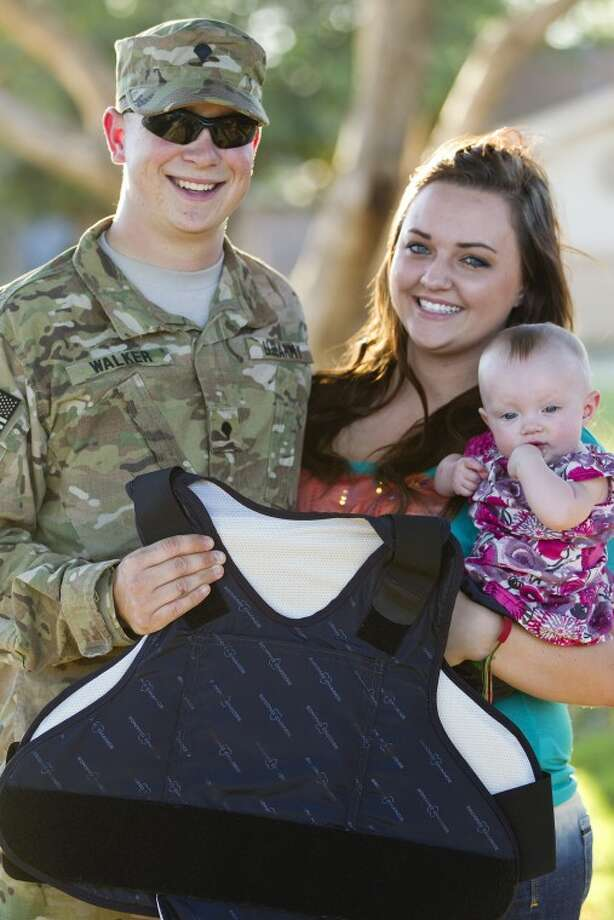 Texas Army National Guard Specialist Shane Walker stands with his wife Shelby and 9-month-old daughter Jennifer as he holds a light armor kevlar vest he was given by the Sheriff's Office through a collection of personal donations. The vest offers concealed protection for Walker to wear under his uniform while deployed in Afghanistan. James Durbin/Reporter-Telegram Photo: JAMES DURBIN
