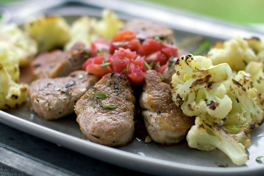 This Aug. 22, 2011 photo shows medallions of pork tenderloin, roasted cauliflower and chunky applesauce in Concord, N.H. Rocco DiSpirito uses Gala apples in this recipe, but suggests trying other apple varieties as well. (AP Photo/Matthew Mead) Photo: MATTHEW MEAD / FR170582 AP