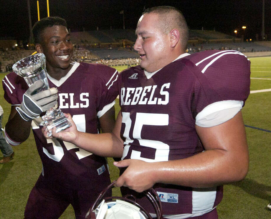 Lee High's Relandas Swan (34) and Vincent Machuca (95) hold the game trophy after a win against EP Coronado Friday at Grande Communications Stadium. James Durbin/Reporter-Telegram Photo: JAMES DURBIN