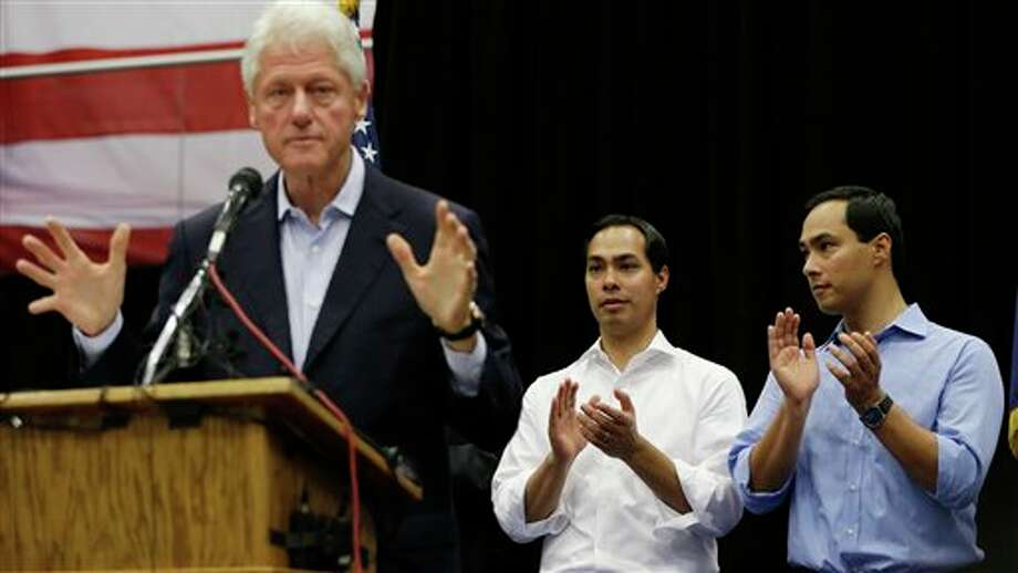 San Antonio Mayor Julian Castro, center, and U.S. congressional hopeful Joaquin Castro, right, listen to former president Bill Clinton during a campaign rally, Thursday, Oct. 25, 2012, in San Antonio. (AP Photo/Eric Gay) Photo: Eric Gay / AP