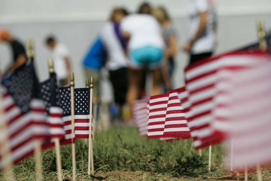 A finished row of flags stands erect Monday as volunteers work to complete the temporary memorial at Midland Classical Academy for the 2,978 victims of the 9/11 attacks.