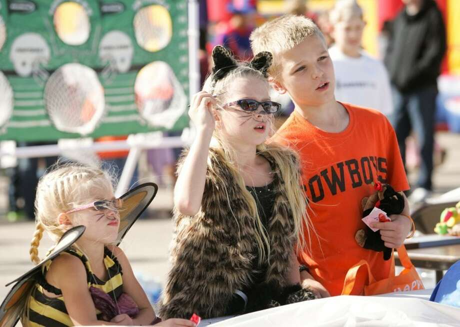Joey Royer, left, and her brother Ian, 10, watch as their sister Kathryn, 8, attempt to pop a balloon with her dart to win a prize during last year's fall festival at Harvest Time Church of the Permian Basin. Cindeka Nealy/Reporter-Telegram Photo: Cindeka Nealy