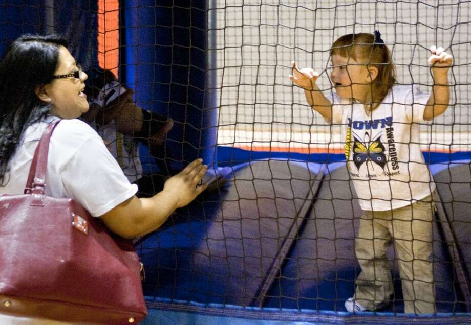 Anita Gomez shares a laugh with Norah Boswell, age 3, at a bounce house set up in the First Baptist Church gym during an event to spread awareness about Down Syndrome Saturday. James Durbin/Reporter-Telegram Photo: JAMES DURBIN