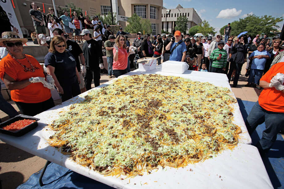 "In this Saturday Sept. 10, 2011 photo released by the New Mexico Tourism Department, residents help build what state officials are calling the ""world's largest Navajo taco,"" in Gallup, N.M. Organizers say no world record exists for the largest Navajo taco so they built one using 150 pieces of fry bread and 30 pounds of green chile. According to volunteers and state officials, the Navajo taco created Saturday was more than 10 feet in diameter and also needed 65 pounds of ground beef, 65 pounds of beans, 50 pounds of lettuce and 90 pounds of cheese. (AP Photo/New Mexico Tourism Department) Photo: HOPD / New Mexico Tourism Departmen"