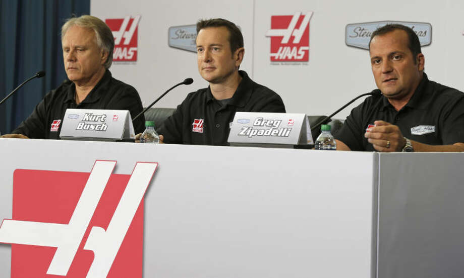 Team co-owner Gene Haas, left, and driver Kurt Busch, center, watch as competition director Greg Zipadelli, right, answers a question during an auto racing news conference in Kannapolis, N.C., Tuesday, Aug. 27, 2013. Stewart Haas Racing announced that Busch will be the driver of their fourth Sprint Cup Series auto racing team in 2014. (AP Photo/Chuck Burton) Photo: Chuck Burton