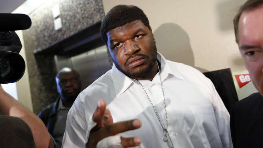 """FILE - In this Dec. 18, 2012 file photo, Dallas Cowboys defensive tackle Josh Brent, center, and his attorney George Miller, obscured at right, leave court in Dallas. Brent says he is retiring from football as he faces trial for a fatal crash that killed a teammate. Brent's agent, Peter Schaffer, said Thursday, July 18, 2013, that the 25-year-old Brent was """"taking care of his priorities."""" (AP Photo/David Woo, Pool, File) Photo: David Woo"""