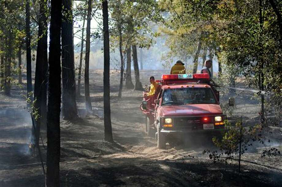 In this Sept. 11, 2011 photo, a crew from Whitehouse looks for flames to extinguish during a wildfire near Mixon, Texas. Fed by howling winds whipped up by the remnants of Tropical Storm Lee, flames streaked across drought-stricken Texas, where more than 190 fires statewide have killed four people. The worst damage was in Bastrop, where two smaller fires joined to form a monster blaze that has destroyed more than 1,550 homes and charred more than 34,000 acres. (AP Photo/The Tyler Morning Telegraph, Sarah A. Miller) Photo: Sarah A. Miller / Sarah A. Miller | Tyler Morning Telegraph