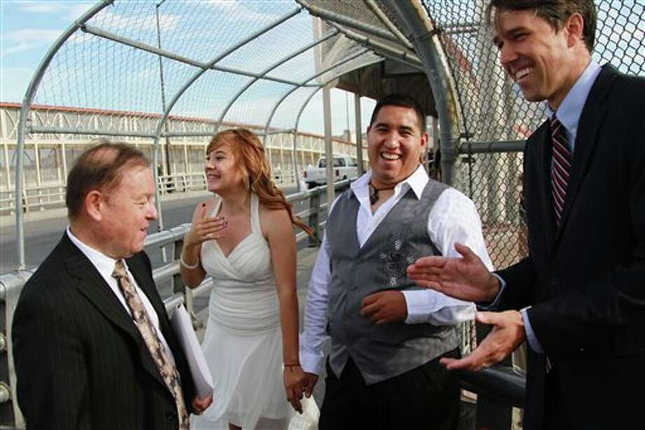 U.S. citizen Edgar Falcon, second from right, and Maricruz Valtierra of Mexico, second from left, laugh while El Paso congressman Beto O'Rourke, right, and Judge Bill Moody, left, congratulate them after the couple was married at U.S.-Mexico border, Tuesday, Aug. 27, 2013 in El Paso, Texas. Like many other couples made up of a US citizen and a foreigner, Falcon and Valtierra, who has been declared inadmissible after an immigration law violation, hope immigration reform will help them live together in the U.S. (AP Photo/Juan Carlos Llorca) Photo: Juan Carlos Llorca / AP