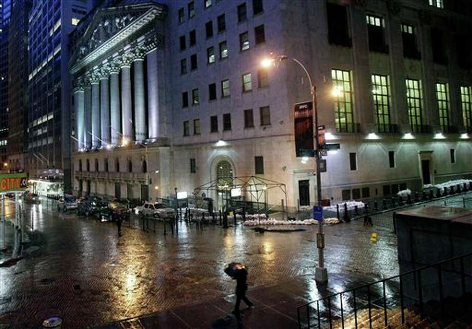 Sand bags protect the front of the New York Stock Exchange, Monday, Oct. 29, 2012. Hurricane Sandy continued on its path Monday, forcing the shutdown of mass transit, schools and financial markets, sending coastal residents fleeing, and threatening a dangerous mix of high winds and soaking rain. There had been plans to allow electronic trading to go forward on the New York Stock Exchange but with a storm surge expected to cover parts of lower Manhattan in water, officials decided late Sunday that it was too risky to ask any personnel to staff the exchanges. (AP Photo/Richard Drew) Photo: Richard Drew / AP