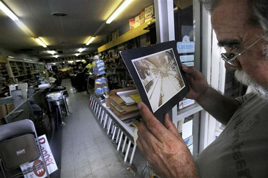 In this Aug. 23, 2013 photo, Joe Pete Forcher compares a 100-year-old photo of Dean Rexall Drug to the way the interior currently looks in Cisco, Texas. Although the store closed in 1999, an estate sale during last weekend of August will allow the public to see decades worth of patent medicines, old cameras and an X-ray machine. (AP Photo/The Abilene Reporter-News, Ronald W. Erdrich) Photo: Ronald W. Erdrich / The Abilene Reporter-News