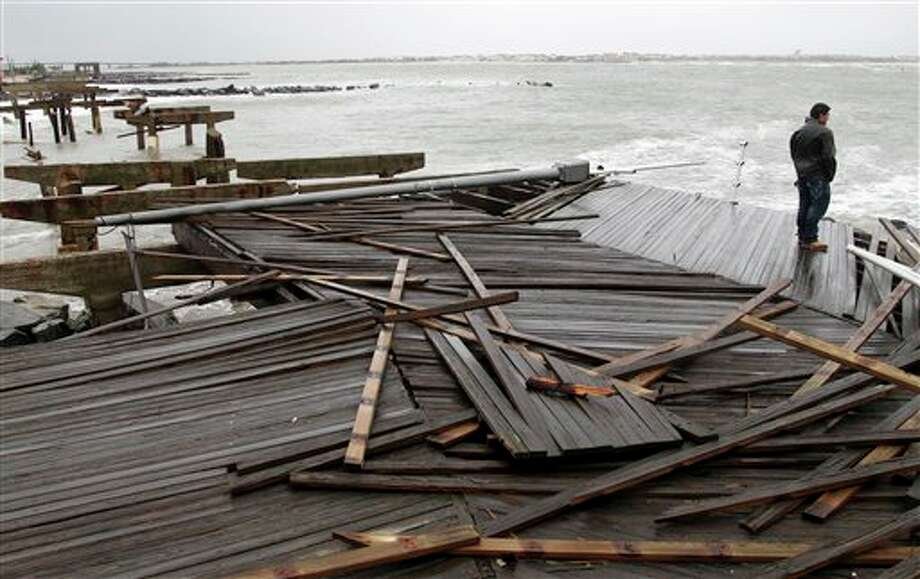 Nicholas Rodriguez looks over a section of the destroyed boardwalk in Atlantic City, N.J., Tuesday, Oct. 30, 2012, not far from where a powerful storm that started out as Hurricane Sandy made landfall the night before. Millions of people from Maine to the Carolinas awoke Tuesday without electricity, but the full extent of the damage in New Jersey, where the storm roared ashore Monday night with hurricane force, was unclear. (AP Photo/Seth Wenig) Photo: Seth Wenig / AP2012