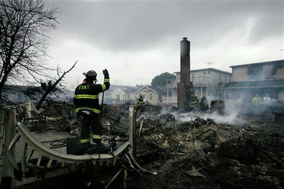 A fire fighter surveys the smoldering ruins of a house in the Breezy Point section of New York, Tuesday, Oct. 30, 2012. More than 50 homes were destroyed in a fire which swept through the oceanfront community during superstorm Sandy. (AP Photo/Mark Lennihan) Photo: Mark Lennihan / The Associated Press2012