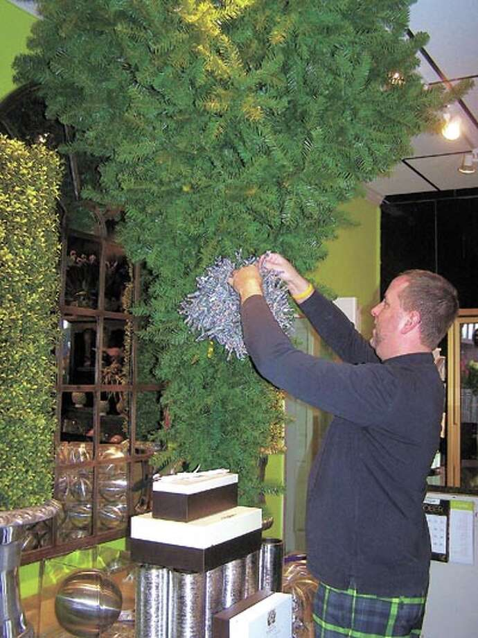 Flowerland's Chris Collum, AIFD, TMF, prepares the showroom for the annual Christmas open house. This year's celebration will be this Sunday from 1-4 p.m. Door prizes, giveaways and refreshments will be ready for you.
