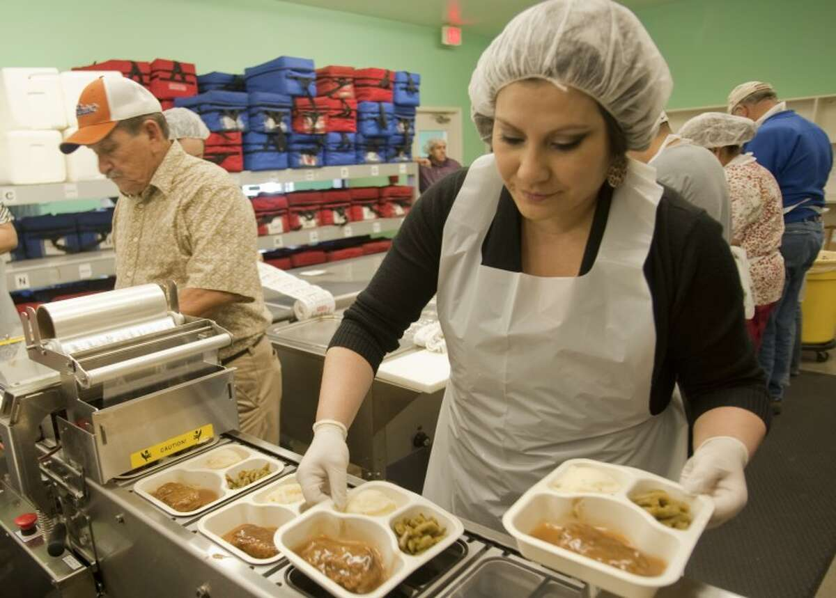 Kris Sifuentes loads trays into the sealer as she and other volunteers prepare meals for Meals on Wheels Wednesday as part of HEB's donation with Feast of Sharing. Tim Fischer\Reporter-Telegram