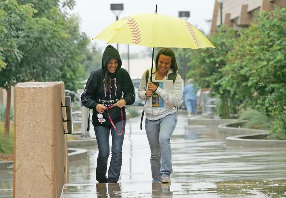 Taylor Clancy, left, and Earnysha Scroggins try to stay dry as they head to their reading lab Thursday at Midland College. Photo: Cindeka Nealy/Reporter-Telegram