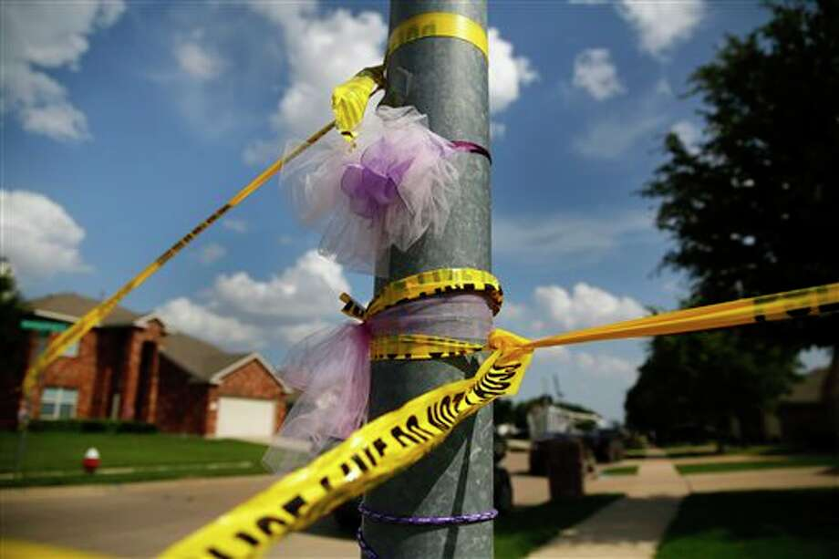 A light pole is wrapped in purple ribbons for slain 6-year-old Alanna Gallagher, and police tape, Tuesday, July 23, 2013, in Saginaw, Texas. Three weeks after a Gallagher's body was found in a trash bag wrapped in a tarp hours after she had been playing outside, authorities went to her teenage neighbor's house looking to arrest him. Instead, the 17-year-old suspect, Tyler Holder, was shot after authorities say he opened fire, seriously wounding a police detective. (AP Photo/The Dallas Morning News, Tom Fox) MANDATORY CREDIT; MAGS OUT; TV OUT; INTERNET USE BY AP MEMBERS ONLY; NO SALES Photo: Tom Fox / Dallas Morning News