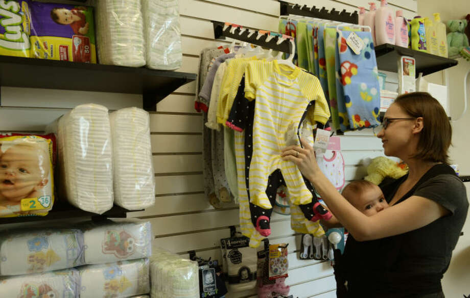 Sarah Taylor and her son Aaron, 4 1/2 months, looks through items available at the newly reopened Hope Chest of Midland inside Midland Memorial West Campus. Tim Fischer\Reporter-Telegram Photo: Tim Fischer