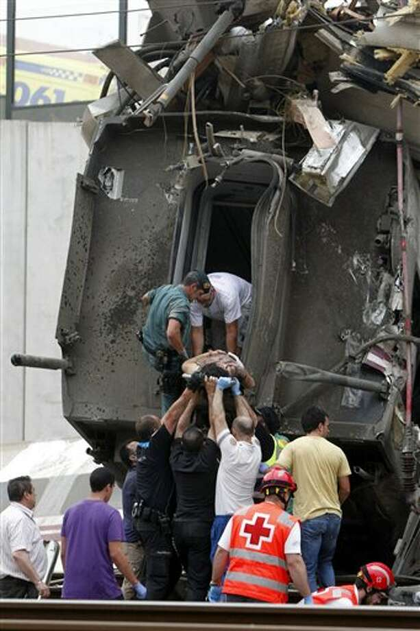 "In this photo taken on Wednesday July 24 2013, A woman is evacuated from a train car at the site of a train accident in Santiago de Compostela, Spain. Spanish police on Friday detained the driver of a train that crashed in northwestern Spain, lowered the death toll from 80 to 78 and took possession of the ""black box"" of the train expected to shed light on why it was going faster than the speed limit on the curve where it derailed. And in an interview with The Associated Press, an American passenger injured on the train said he saw on a TV monitor screen inside his car that the train was traveling 194 kph (121 mph) seconds before the crash — far above the 80 kph (50 mph) speed limit on the curve where it derailed. (AP Photo/La Voz de Galicia/Monica Ferreiros) Photo: La Voz De Galicia/Monica Ferreiros / AP"