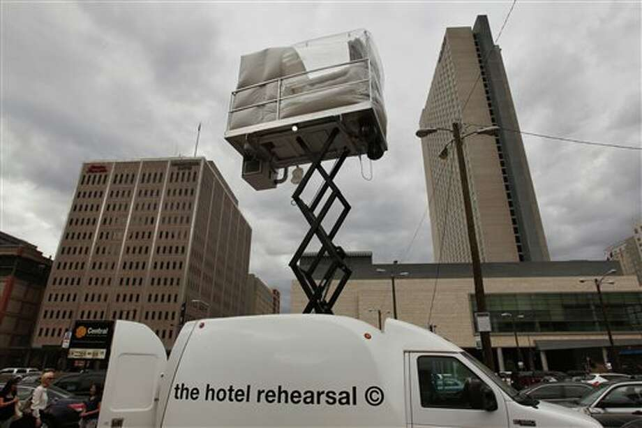 A hotel room made of aluminum and inflated vinyl is held aloft by a van-mounted scissor lift, on promotional display in a parking lot in downtown Denver, Wednesday July 25, 2013. Architectural artist Alex Schweder created the 5 by 7 foot room atop a van for the Biennial of the Americas in Denver. For $50,000, a guest would get one weekend night in the puffy space, plus lots of extras including a diamond pendant and earring set, two iPod Nanos and a dance party for 100 people in a ballroom of The Curtis Hotel. (AP Photo/Brennan Linsley) Photo: Brennan Linsley / AP